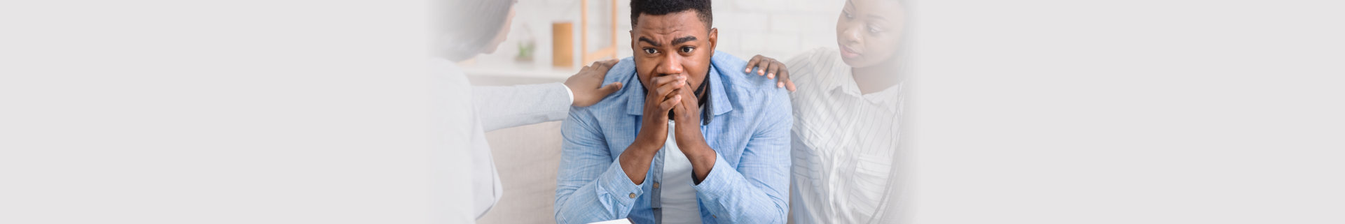 Caring black wife and counselor supporting man during psychotherapy session.